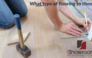 Man kneeling while measuring for a hardwood flooring installation. Flooring, hammer, pencil are also visable.